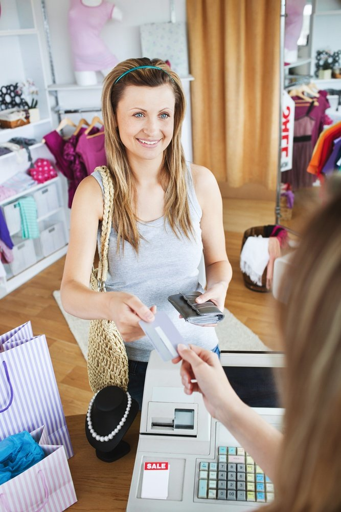 Charming young woman buying clothes with her card in a shop.jpeg