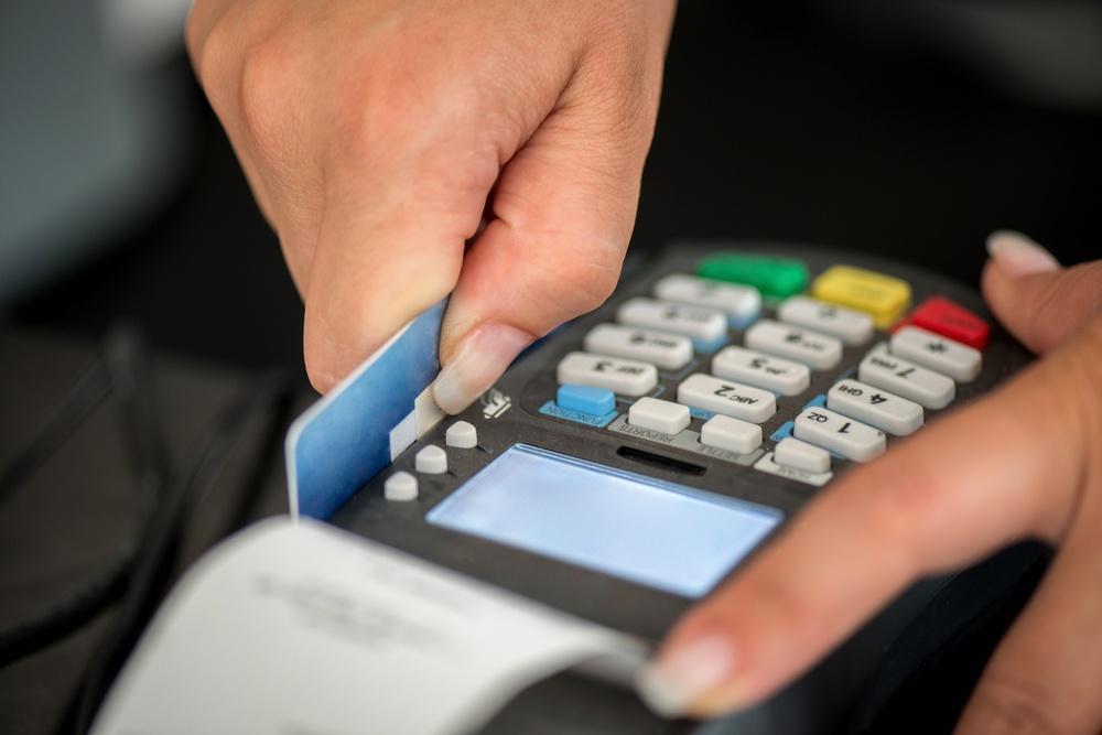 Consumer swiping credit card in POS credit card reader